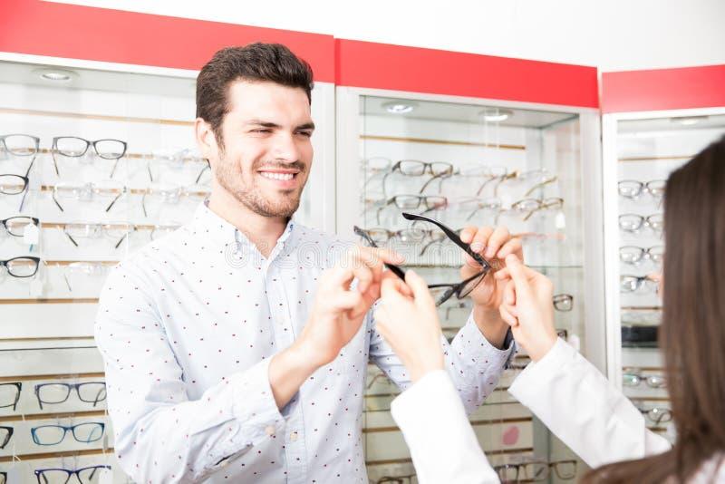 Bakre sikt av kvinnaoptiker som ger glasögon till den stiliga mannen fotografering för bildbyråer
