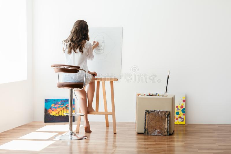 Bakre sikt av kvinnlig konstnärmålning på kanfas i studio arkivbilder