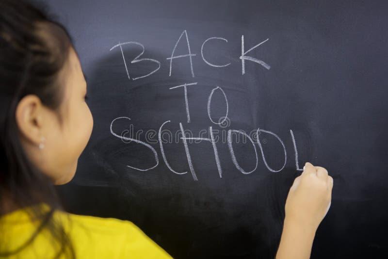 Bakre sikt av lilla flickan som skriver text av baksida till skola royaltyfri fotografi
