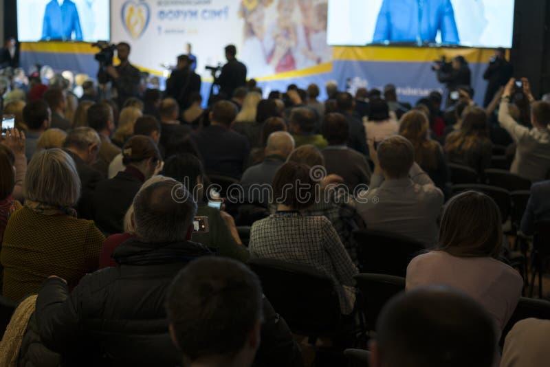 Bakre sikt av lyssnande högtalare för åhörare på etappen i mötet för konferenskorridor eller seminarium, affär och utbild royaltyfri fotografi