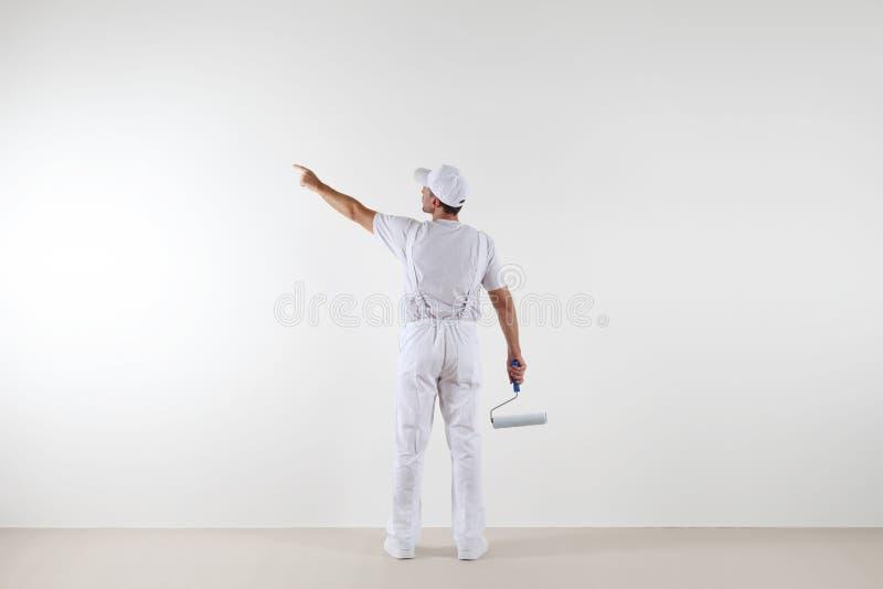 Bakre sikt av målaremannen som pekar med fingret den tomma väggen, wi royaltyfri foto
