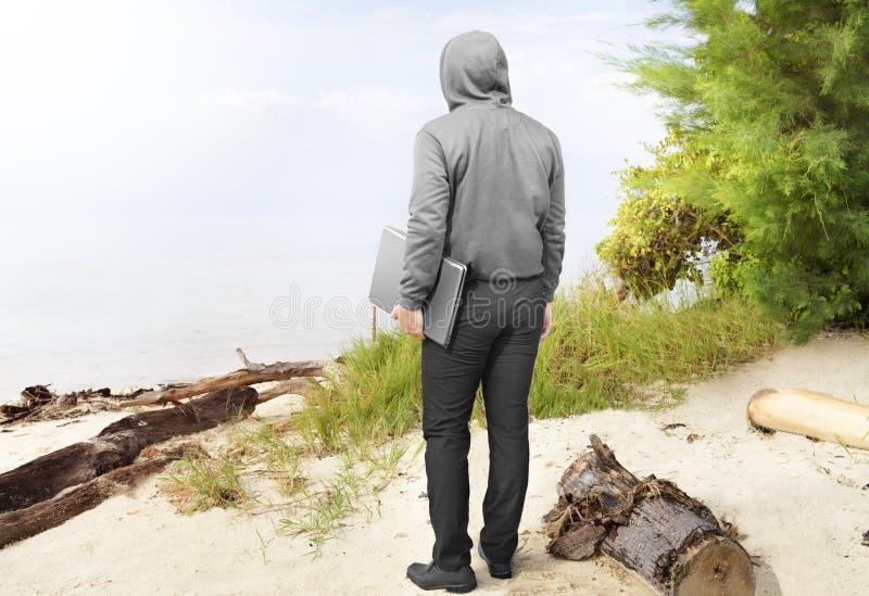 Bakre sikt av mannen i bärande bärbar dator för svart hoodie i hans hand arkivbild