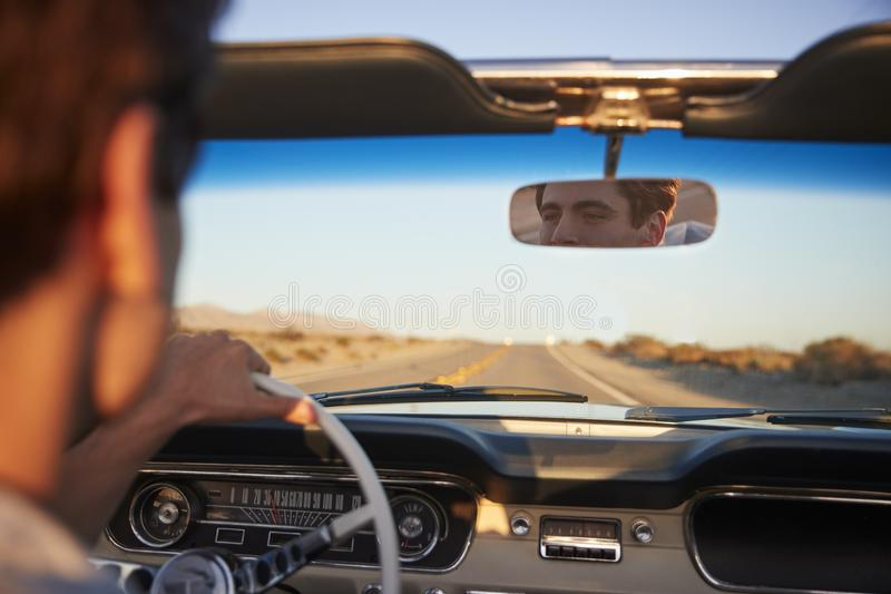 Bakre sikt av mannen på vägturen som kör den klassiska konvertibla bilen in mot solnedgång royaltyfri bild