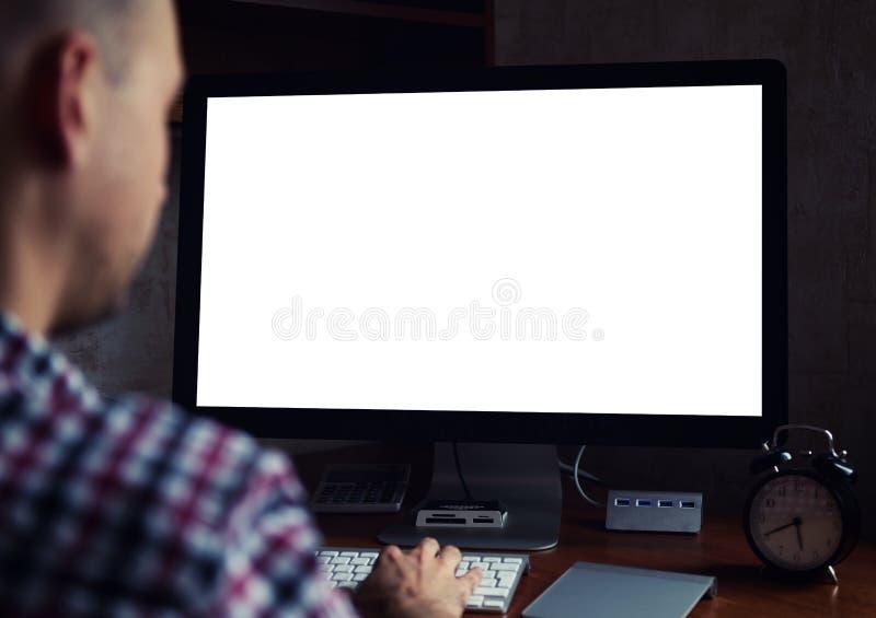 Bakre sikt av mannen som arbetar på datoren på natten arkivfoto