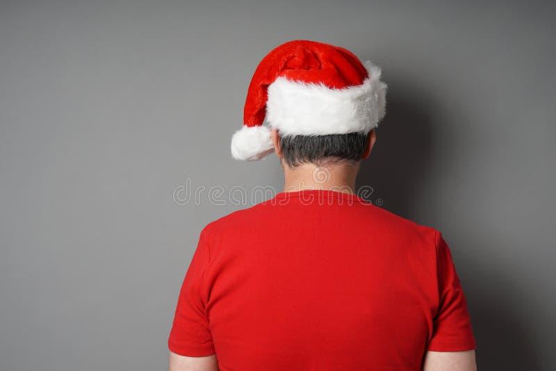 Bakre sikt av mannen som bär den santa hatten och den röda t-skjortan fotografering för bildbyråer