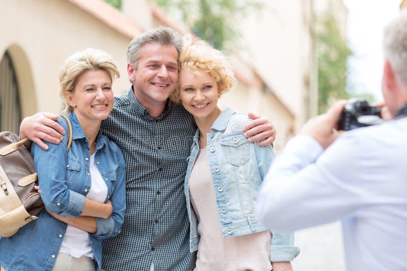 Bakre sikt av mannen som fotograferar manliga och kvinnliga vänner i stad royaltyfri foto