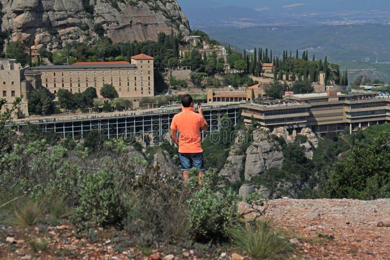 Bakre sikt av mannen som fotograferar sikt av Montserrat berg och Benedictineabbotskloster av Santa Maria de Montserrat på ett bä arkivfoto
