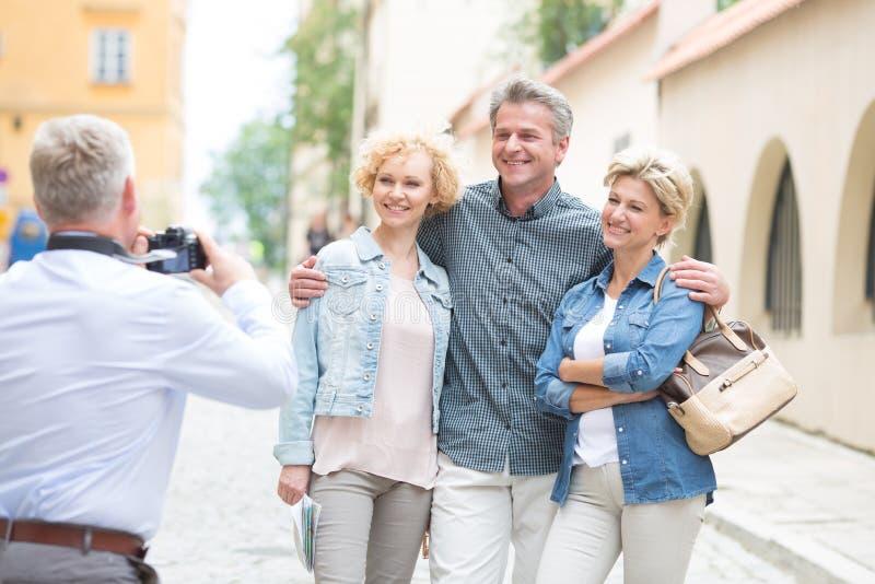 Bakre sikt av mannen som fotograferar vänner i stad royaltyfri bild