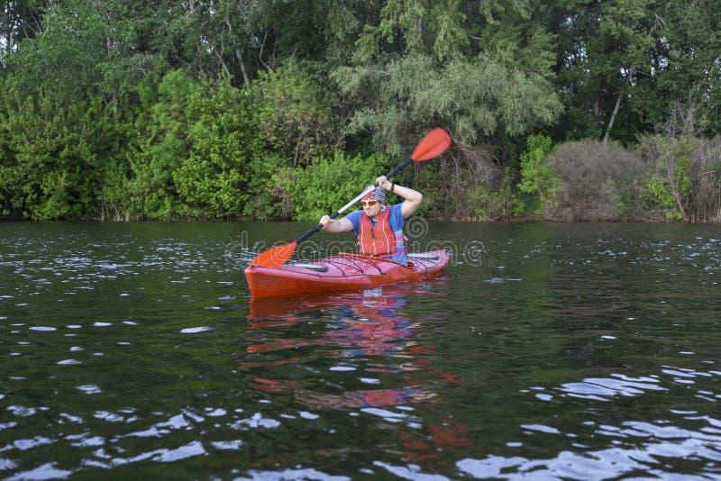 Bakre sikt av mannen som paddlar kajaken i sjön med kvinnan i bakgrund Koppla ihop kayaking i sjön på en solig dag royaltyfria bilder