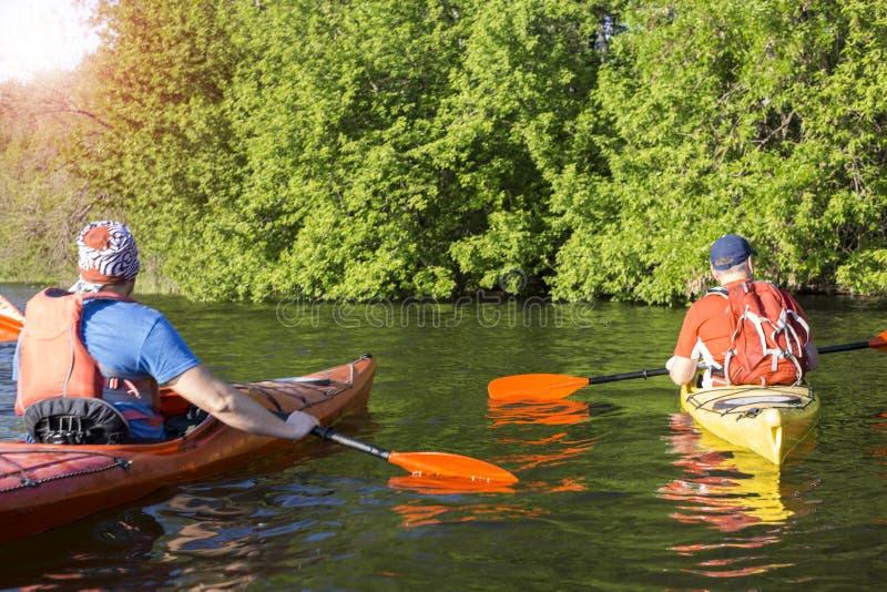 Bakre sikt av mannen som paddlar kajaken i sjön med kvinnan i bakgrund Koppla ihop kayaking i sjön på en solig dag arkivfoton