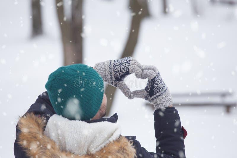 Bakre sikt av mannen som skapade hjärta med händer snöig dag arkivfoton