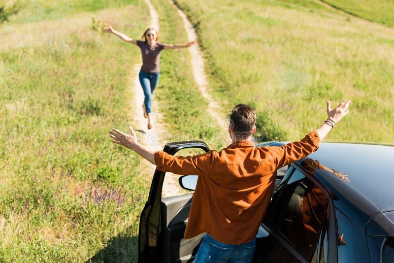 bakre sikt av mannen som står med breda armar nära bilen medan hans flickvän royaltyfri fotografi