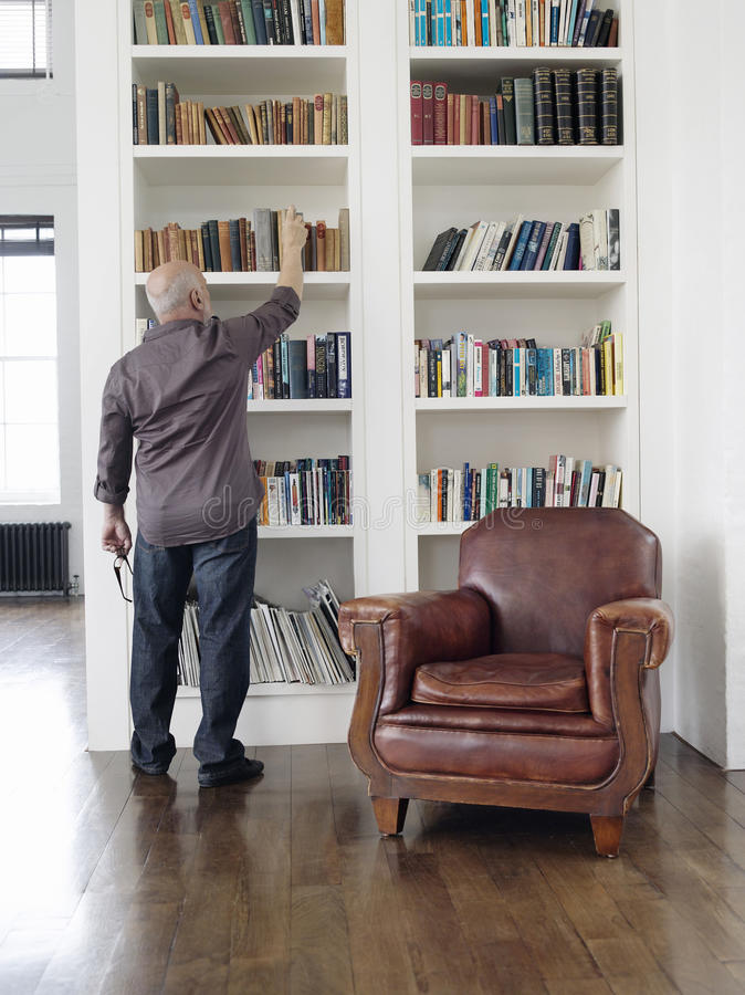 Bakre sikt av mannen som tar boken från hylla royaltyfri foto