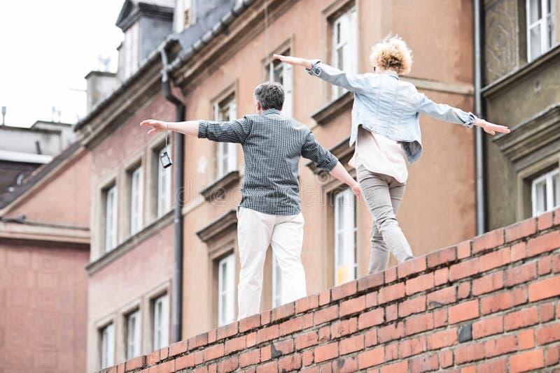 Bakre sikt av medelåldersa par med utsträckt gå för armar på tegelstenväggen royaltyfria bilder