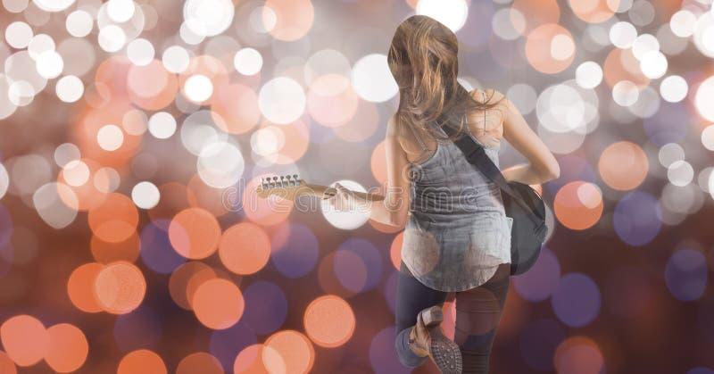 Bakre sikt av musikkonstnären som spelar gitarren över bokeh arkivfoto