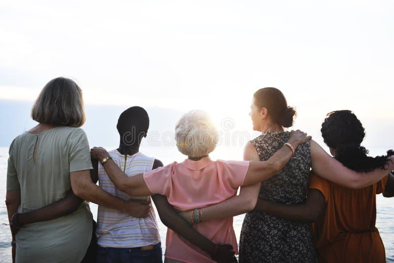 Bakre sikt av olika höga kvinnor som tillsammans står på stranden royaltyfri foto