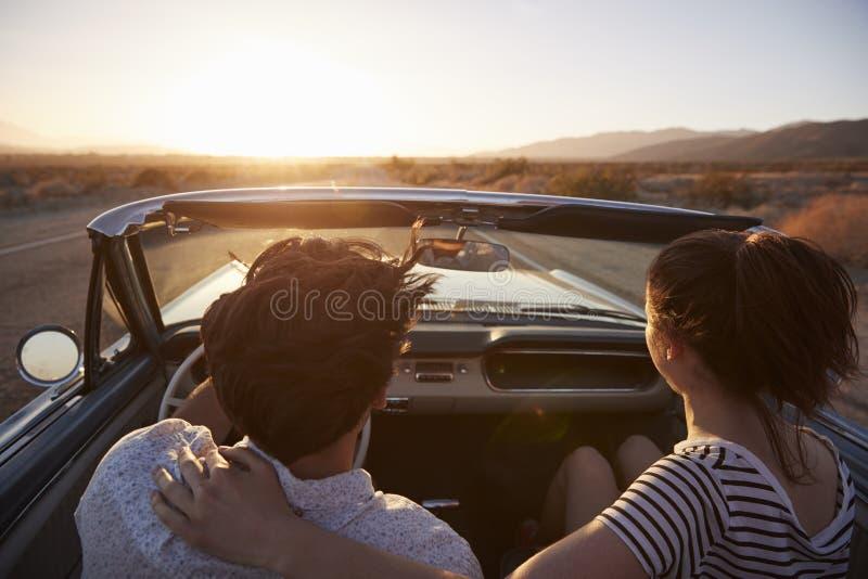 Bakre sikt av par på vägturen som kör den klassiska konvertibla bilen in mot solnedgång fotografering för bildbyråer