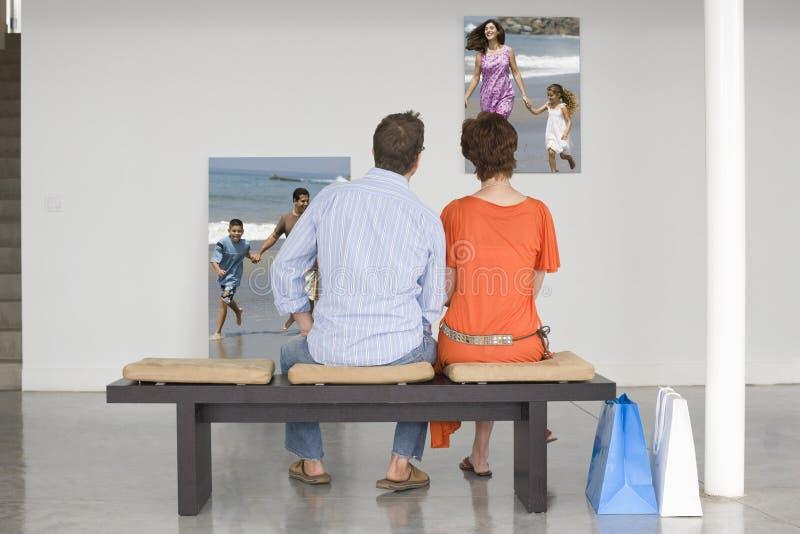Bakre sikt av par som placeras på bänken som ser fotografier som föreställer den framtida planläggningen royaltyfria bilder