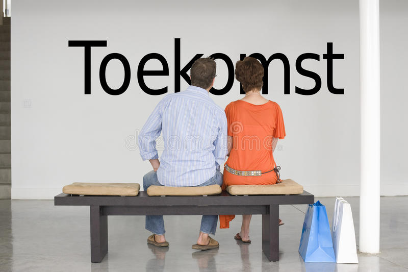 Bakre sikt av par som placeras på läs- holländsk text Toekomst (framtid) för bänk på väggen royaltyfri bild