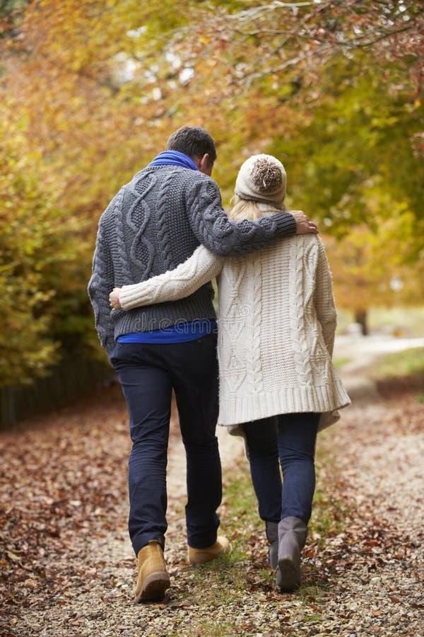 Bakre sikt av par som promenerar Autumn Path arkivbild