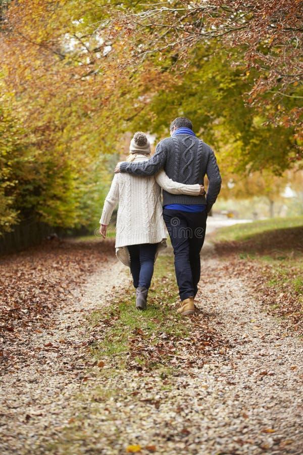Bakre sikt av par som promenerar Autumn Path royaltyfri fotografi