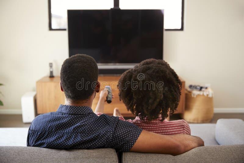 Bakre sikt av parsammanträde på Sofa Watching TV tillsammans royaltyfri fotografi