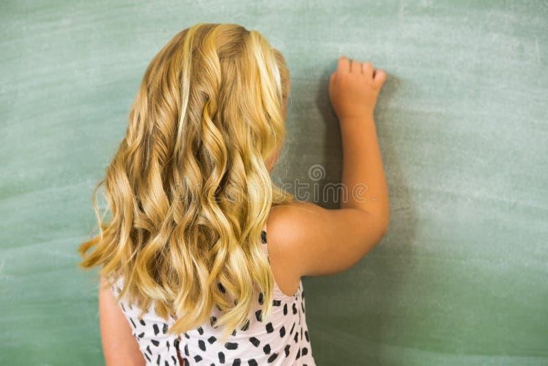 Bakre sikt av skolaflickahandstil på den svart tavlan i klassrum royaltyfri bild
