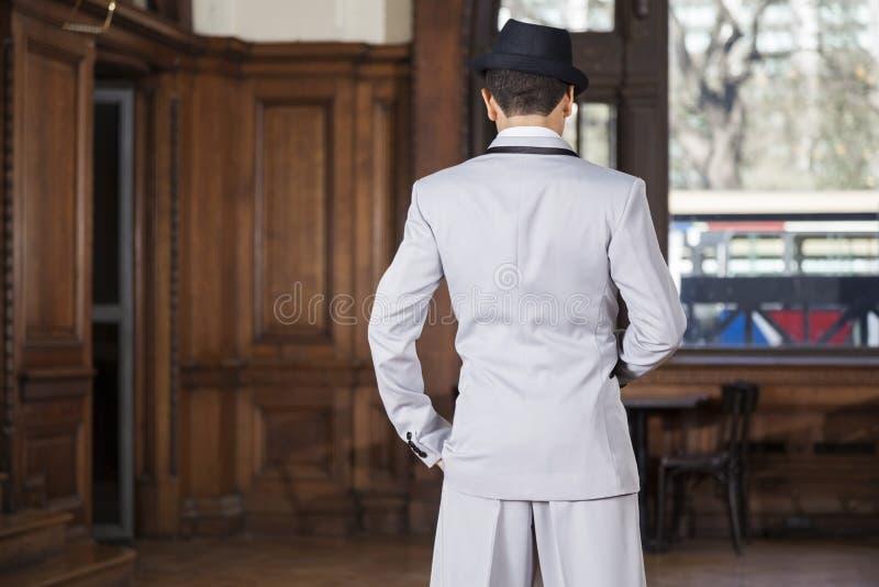 Bakre sikt av tangodansaren Standing In Restaurant arkivfoton