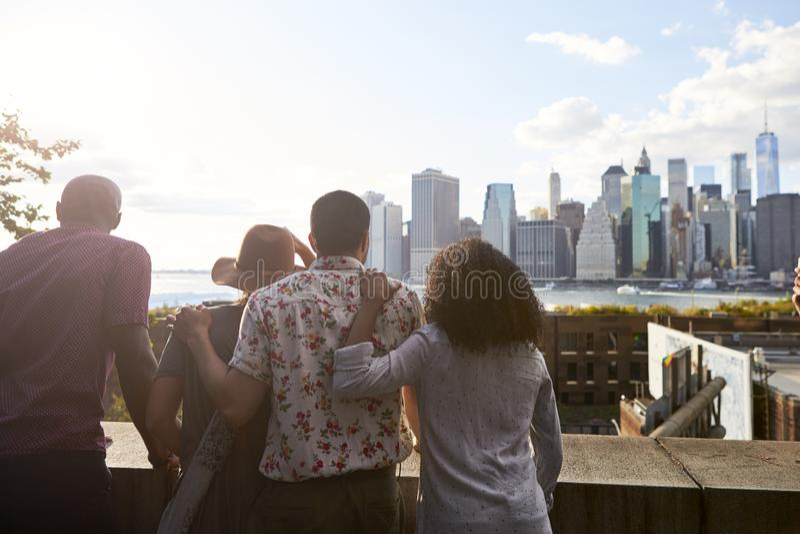 Bakre sikt av turister som ser Manhattan horisont fotografering för bildbyråer