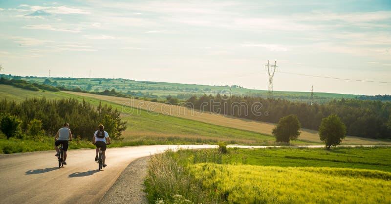 Bakre sikt av tv? cyklister som rider ner landsv?gen till och med berg Tillf?lliga m?n som har gyckel som cyklar ner den tomma v? royaltyfri fotografi