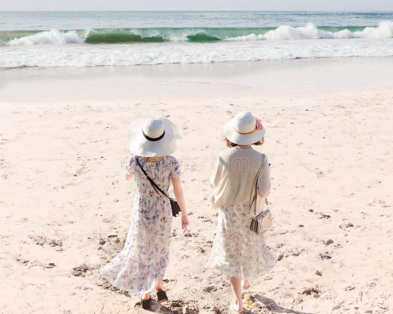 Bakre sikt av två unga kvinnor i långa klänningar och hattar som promenerar den sandiga stranden royaltyfria bilder