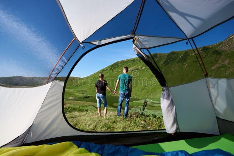 Bakre sikt av två unga turister som vilar nära att campa i berg royaltyfria bilder