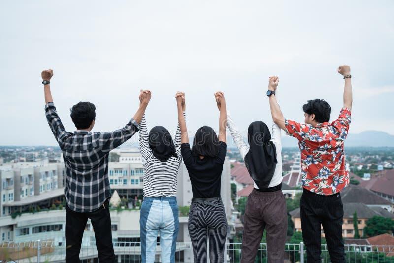 Bakre sikt av unga vänner som tillsammans sitter på tak royaltyfria foton