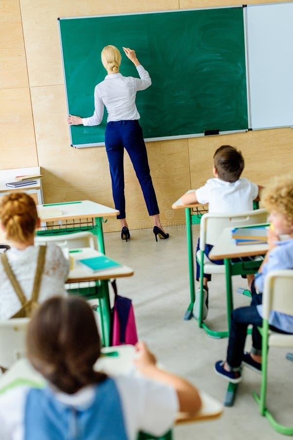 bakre sikt av ungar som ser läraren medan henne som skriver arkivfoton