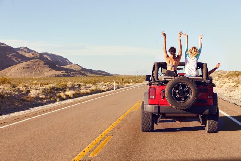 Bakre sikt av vänner på vägturen som kör i konvertibel bil royaltyfri fotografi