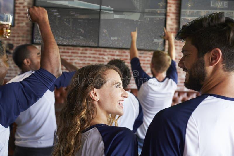 Bakre sikt av vänner som håller ögonen på leken i sportstång på skärmar arkivfoton