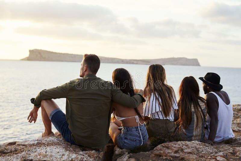 Bakre sikt av vänner som sitter på Cliff Watching Sunset arkivfoto