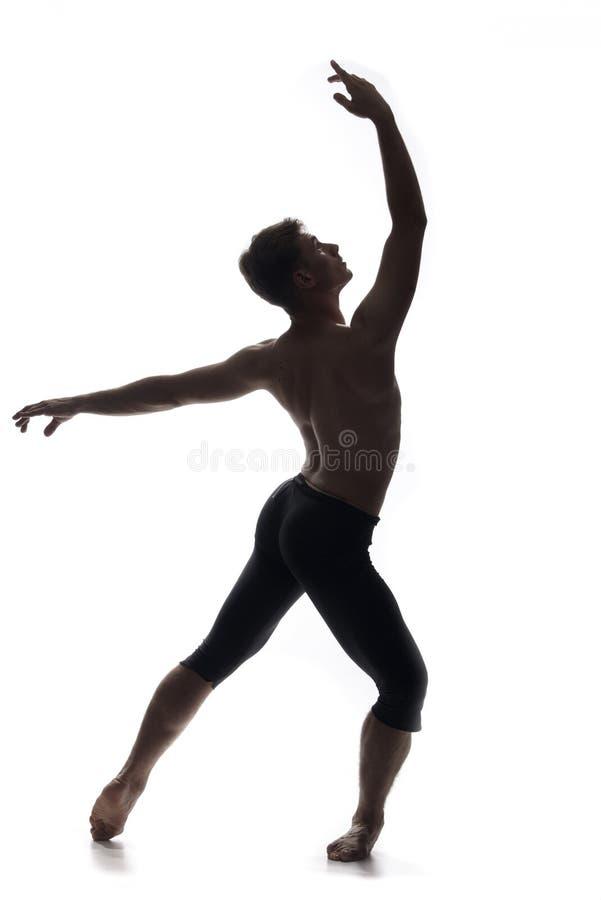 Bakre sikt, en baksida för ung man, balettdansör som poserar att se upp, royaltyfri fotografi