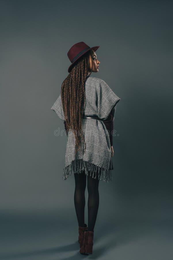 bakre sikt för full längd av den stilfulla unga afrikansk amerikankvinnan i hattanseende arkivfoto