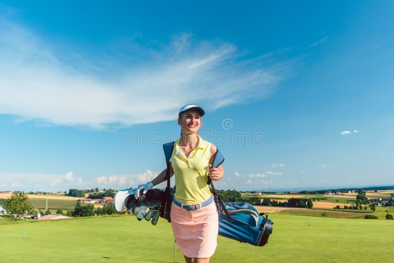 Bakre sikt för full längd av en aktiv kvinna som bär en blå ställningspåse royaltyfria foton