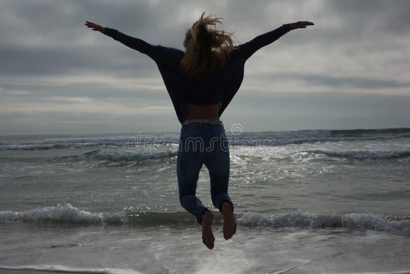 Bakre sikt för full längd av en kvinnabanhoppning på stranden royaltyfri fotografi