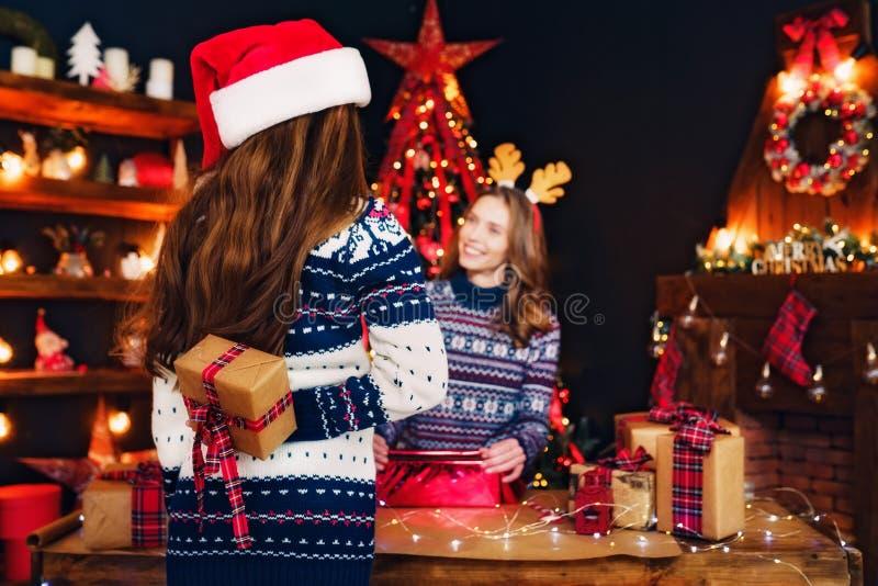 Bakre sikt från baksidan av en gladlynt mamma och hennes gulliga dotterflicka som utbyter gåvor royaltyfri bild
