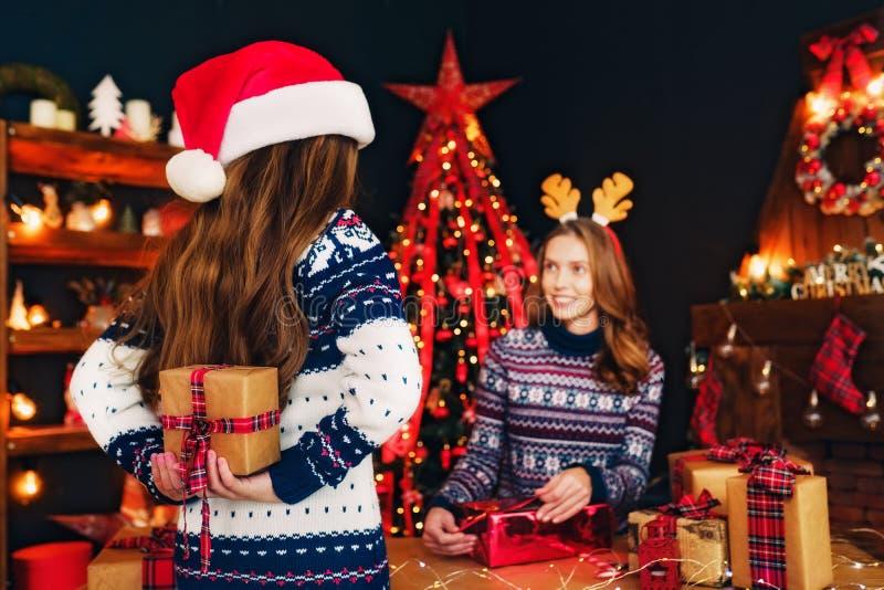 Bakre sikt från baksidan av en gladlynt mamma och hennes gulliga dotterflicka som utbyter gåvor royaltyfria bilder