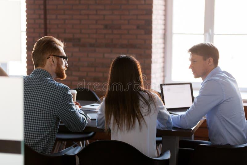 Bakre sikt på affärslagfolk som talar på kontorsmötet arkivfoto