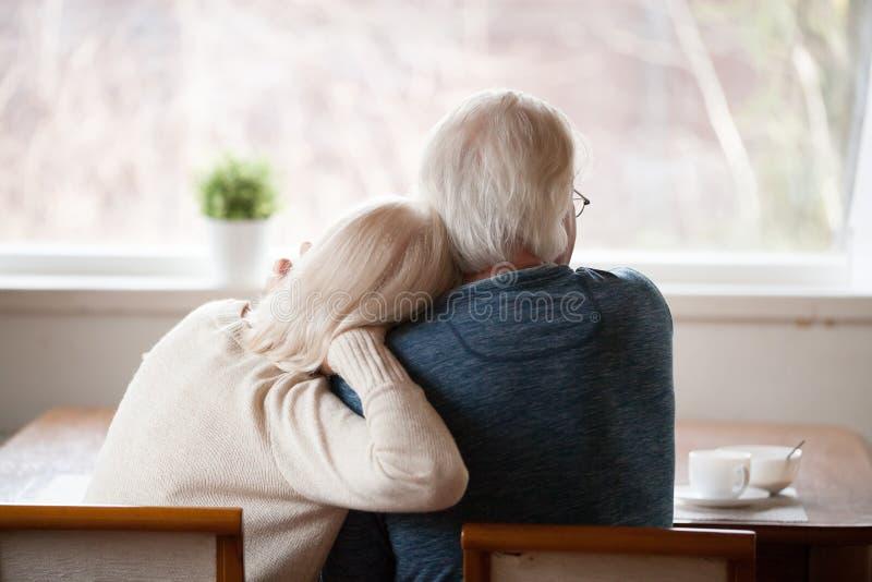 Bakre sikt på höga gråa haired par som hemma kopplar av arkivfoton