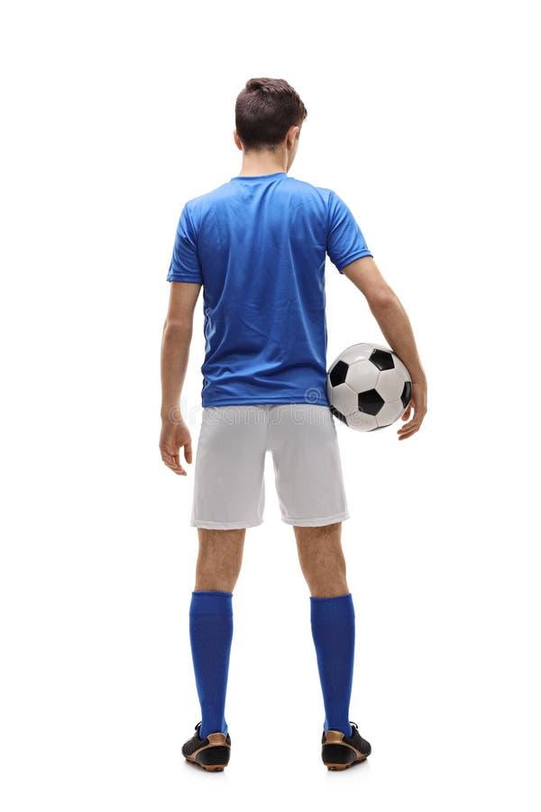 Bakre sikt som skjutas av en tonårs- fotbollsspelare arkivbild