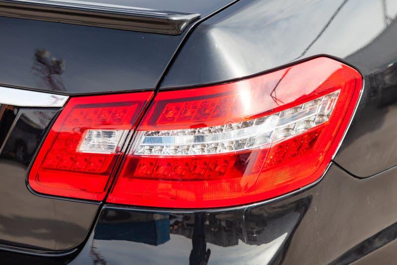 Bakre taillampsikt för svart bil med mörkt - grå inre i utmärkt villkor i en parkeringsplats bland andra bilar royaltyfri fotografi