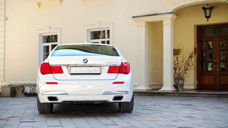 Bakre tillbaka sikt för modern lyxig BMW 750Li XDrive bil som parkeras på sten stenlagd parkering nära det horisontalforntida hus arkivfoto