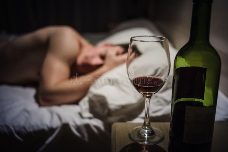 Bakrusman med huvudvärker i en säng på natten fotografering för bildbyråer
