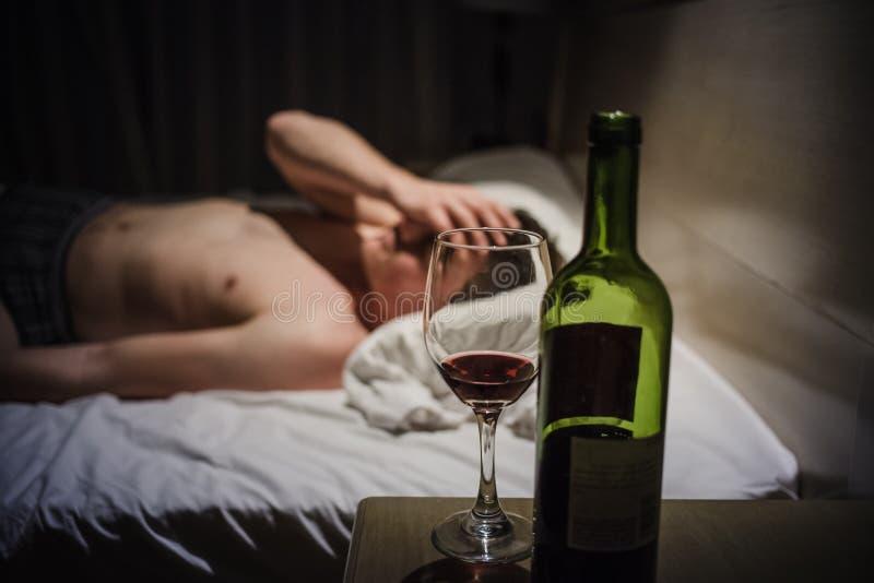 Bakrusman med huvudvärker i en säng på natten arkivfoto